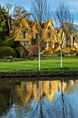 ABLINGTON MANOR, GLOUCESTERSHIRE: VIEW ACROSS RIVER COLN TO MANOR HOUSE. MARCH, EARLY SPRING, LATE WINTER, WATER, RIVER, COUNTRY, GARDEN, ENGLISH, TOPIARY