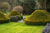 ABLINGTON MANOR, GLOUCESTERSHIRE: LAWN WITH CLIPPED TOPIARY YEW AROUND STONE SUNDIAL - CLASSIC COUNTRY GARDEN, SUMMER, MARCH, FOCAL POINT