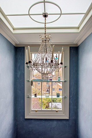LONDON_HOUSE_DESIGNED_BY_JULIE_SIMONSEN_CHANDELIER_IN_STAIRWELL_WITH_SHELVED_WINDOW_DISPLAYING_GLASS