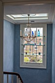 LONDON HOUSE DESIGNED BY JULIE SIMONSEN. CHANDELIER IN STAIRWELL WITH SHELVED WINDOW DISPLAYING GLASS ORNAMENTS.