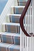 LONDON HOUSE DESIGNED BY JULIE SIMONSEN. DETAIL OF STAIRS WITH WOODEN BANNISTER AND BLUE AND BROWN CHECKED STAIR RUNNER.