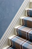 LONDON HOUSE DESIGNED BY JULIE SIMONSEN. DETAIL OF BLUE POLISHED PLASTER WALL WITH BLUE AND BROWN CHECKED STAIR RUNNER