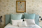 LONDON HOUSE DESIGNED BY JULIE SIMONSEN. BLUE BEDROOM WITH ANTIQUE PAINTING ON WALL. WALLPAPER BY COLEFAX & FOWLER