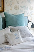 LONDON HOUSE DESIGNED BY JULIE SIMONSEN. BLUE BEDROOM WITH DETAIL OF CUSHIONS AND BEDLINEN. WALLPAPER BY COLEFAX & FOWLER