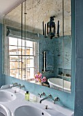 LONDON HOUSE DESIGNED BY JULIE SIMONSEN. VERRE EGLOMISE MIRROR ABOVE DOUBLE BASINS IN BLUE BATHROOM