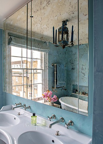 LONDON_HOUSE_DESIGNED_BY_JULIE_SIMONSEN_VERRE_EGLOMISE_MIRROR_ABOVE_DOUBLE_BASINS_IN_BLUE_BATHROOM