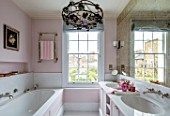 LONDON HOUSE DESIGNED BY JULIE SIMONSEN. THE PINK BATHROOM WITH PANELLED BATH AND DOUBLE BASINS WITH DUTCH ANTIQUE CHANDELIER.