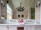 LONDON HOUSE DESIGNED BY JULIE SIMONSEN. PINK BATHROOM WITH DOUBLE BASINS. REFLECTION OF ANTIQUE CHANDELIER IN FAUX VERRE EGLOMISE MIRROR