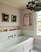 LONDON HOUSE DESIGNED BY JULIE SIMONSEN. PINK BATHROOM. PALE PINK PANELLED BATH WITH TOWEL RAIL AND ANTIQUE FLOWER PRINTS DISPLAYED ON WALL