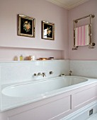 LONDON HOUSE DESIGNED BY JULIE SIMONSEN. PINK BATHROOM. PANELLED BATH WITH TOWEL RAIL AND ANTIQUE FLOWER PRINTS DISPLAYED ON WALL