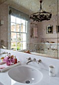 LONDON HOUSE DESIGNED BY JULIE SIMONSEN. PINK BATHROOM. CHERRY BLOSSOM ON TRAY WITH FAKE VERRE EGLOMISE MIRROR AND MARBLE SINK SURROUND