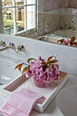 LONDON HOUSE DESIGNED BY JULIE SIMONSEN. PINK BATHROOM. CHERRY BLOSSOM ON TRAY WITH FAKE VERRE EGLOMISE MIRROR AND MARBLE SURROUND