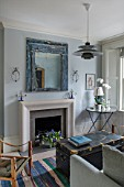 LONDON HOUSE DESIGNED BY JULIE SIMONSEN. THE LIVING ROOM DECORATED IN SHADES OF BLUE WITH NEW SANDSTONE FIREPLACE SURROUND. DISTRESSED BLUE MIRROR AND VINTAGE TRUNK USED AS COFFEE TABLE.
