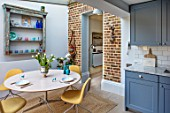 LONDON HOUSE DESIGNED BY JULIE SIMONSEN. MORNING ROOM ADJACENT TO KITCHEN WITH CIRCULAR TABLE AND CONTEMPORARY YELLOW CHAIRS. AZURE BLUE KITCHEN BY LAURENCE PIDGEON