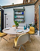 LONDON HOUSE DESIGNED BY JULIE SIMONSEN. MORNING ROOM WITH EXPOSED BRICKWORK AND CIRCULAR TABLE WITH CONTEMPORARY YELLOW CHAIRS. LEADING OUT TO GARDEN.