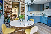 LONDON HOUSE DESIGNED BY JULIE SIMONSEN. AZURE BLUE KITCHEN BY LAURENCE PIDGEON WITH LA CORNUE RANGE OVEN ADJACENT TO MORNING ROOM WITH EXPOSED BRICKWORK AND CIRCULAR TABLE AND YELLOW CHAIRS.