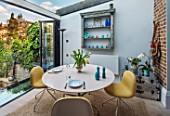 LONDON HOUSE DESIGNED BY JULIE SIMONSEN. MORNING ROOM WITH GLASS BIFOLD DOORS  LEADING TO GARDEN. CIRCULAR TABLE LAID FOR BREAKFAST WITH CONTEMPORARY YELLOW CHAIRS. DISTRESSED WALL SHELF AND COLOURED GLASSWARE