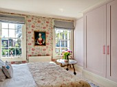 LONDON HOUSE DESIGNED BY JULIE SIMONSEN. GUEST BEDROOM WITH PAINTING OF YOUNG GIRL FOUND AT PARISIAN ANTIQUES DEALER. JULIE DECORATED THE WHOLE ROOM AROUND HER. WALLPAPER BY OSBORNE & LITTLE. QUILTED ANTIQUE WELSH COVERLET. CONTEMPORARY RESIN HANDLES ON WARDROBE FROM SHOP DECO