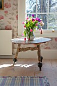LONDON HOUSE DESIGNED BY JULIE SIMONSEN. TABLE WITH VASE OF TULIPS IN PINK GUEST ROOM IS A HAND-PAINTED ANTIQUE FROM ONE OF THE BALTIC STATES. WALLPAPER BY OSBORNE & LITTLE