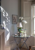LONDON HOUSE DESIGNED BY JULIE SIMONSEN. CORNER OF LIVING ROOM WITH SHUTTERED WINDOWS AND VINTAGE CIRCULAR TABLE WITH ORCHID AND LAMP