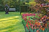 PASHLEY MANOR GARDEN, EAST SUSSEX. SPRING, BORDER, TULIPS - TULIPA BALLERINA, TULIPA ILE DE FRANCE. BULBS, COUNTRY, ORANGE, RED, FLOWERS, FAMILY CIRCLE SCULPTURE BY JOHN BROWN