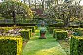 PASHLEY MANOR GARDEN, EAST SUSSEX. SPRING - THE WALLED GARDEN - PATH, BOX HEDGING, BLOSSOM TREES, TULIP ANGELIQUE. TERRACOTTA CONTAINER, HEDGE, HEDGES, APRIL