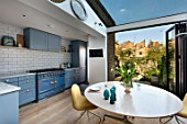 LONDON HOUSE DESIGNED BY JULIE SIMONSEN. AZURE BLUE KITCHEN BY LAURENCE PIDGEON WITH LA CORNUE RANGE OVEN, LEADING TO GARDEN