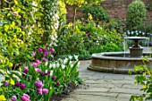 MORTON HALL, WORCESTERSHIRE: SPRING, APRIL, PATH WITH TULIPS, WATER FOUNTAIN, ARCH WITH CLEMATIS. CLASSIC, FORMAL, ENGLISH, COUNTRY, GARDEN