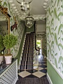 BUTTER WAKEFIELD HOUSE, LONDON. THE HALLWAY. ENTRANCE WITH PALM FROND DECORATED WALLPAPER AND STRIPED CARPET ON STAIRS. MIRROR