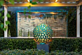 DAVID HARBER SUNDIALS: CHELSEA 2017. MANTLE SCULPTURE IN FRONT OF BRONZE WAVE WATER WALL .WATER FEATURE, CONTEMPORARY, LIGHTING, LIT, LIGHT, MODERN, ART, DESIGN, CRAFT