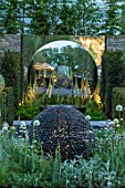 DAVID HARBER SUNDIALS:CHELSEA 2017.DARK PLANET(STONE) & TORUS(MIRRORED METAL) SCULPTURES WITH WHITE PLANTING OF FOXGLOVES,ALLIUMS AND STACHYS. NIGHT,EVENING,LIGHTING,LIT,ART,DESIGN
