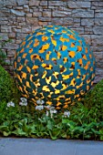 DAVID HARBER SUNDIALS: CHELSEA 2017. MANTLE SCULPTURE. METAL GARDEN SPHERE-LATTICEWORK OF BRONZE PETALS GILDED ON THE INSIDE. FEATURE,DESIGN,ART,CRAFT,LIGHTING,LIT,NIGHT