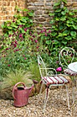 THE CONIFERS, OXFORDSHIRE: DESIGNER CLIVE NICHOLS - SMALL COURTYARD GARDEN - TABLE, CHAIRS, WATERING CAN, STIPA TENUISSIMA, WALL, CIRSIUM RIVULARE ATROPURPUREUM, VITIS COIGNETIAE