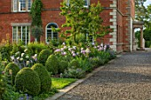 MORTON HALL, WORCESTERSHIRE: GRAVEL PATH, SOUTH GARDEN, CLIPPED YOPIARY BOX, LAWN, IRISES. SUMMER, SPRING, HERBACEOUS, BORDERS, PEONY, PEONIES