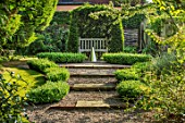 COTTAGE ROW, DORSET: GRAVEL PATH TO YEW ARCH WITH WOODEN SEAT, BENCH, BOX HEDGING, WATER FEATURE, GREEN, FOCAL POINT, ORNAMENT