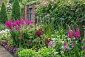 COTTAGE ROW, DORSET: BRICK PATH AND BORDER, SPRING, ALLIUMS, GLADIOLUS COMMUNIS SUBSP. BYZANTINUS, WALL, MORNING