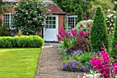 COTTAGE ROW, DORSET: BRICK PATH AND BORDER, SPRING, ALLIUMS, GLADIOLUS COMMUNIS SUBSP. BYZANTINUS, WALL, HOUSE, MORNING, DOOR, LAWN