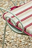 THE CONIFERS, OXFORDSHIRE: GRAVEL, GARDEN, COTSWOLDS, DETAIL OF CHAIR WITH CUSHION. PINK, GREEN, COURTYARD