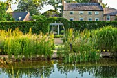 THE OLD RECTORY, QUINTON, NORTHAMPTONSHIRE: DESIGNER ANOUSHKA FEILER: NATURAL SWIMMING POND, HOUSE, WILDFLOWER MEADOW, ARCH THROUGH CARPINUS BETULUS HEDGE. HEDGING, HEDGES