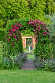 COTTAGE ROW, DORSET: ARCH WITH CLEMATIS MADAME JULIA CORREVON, SUNDIAL AND WALL. FRAMED, VIEW, BRIGHT, PINK, PETALS, FLOWERS, CLIMBERS, CLIMBING