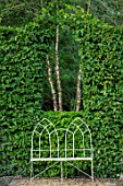 THE OLD RECTORY, QUINTON, NORTHAMPTONSHIRE: DESIGNER ANOUSHKA FEILER: WHITE METAL SEAT, BENCH AND ARCH CUT IN BEECH HEDGE. HEDGING, HEDGES, CLIPPED
