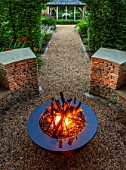 THE OLD RECTORY, QUINTON, NORTHAMPTONSHIRE: DESIGNER ANOUSHKA FEILER: FIRE GARDEN. METAL FIRE PIT, SCULPTURE BY CATHY AZRIA. LIGHTING, LIT UP, NIGHT. WALL, ORNAMENT, DRY, STONE