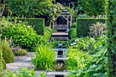 WOLLERTON OLD HALL, SHROPSHIRE: RILL, CANAL, WOODEN PERGOLA, ARBOUR, BENCH, SEAT, POOL, RECTANGULAR, WATER, HEDGES, HEDGING, SUMMER, REFLECTIONS, AXIS, SYMMETRY, FOCAL, POINT