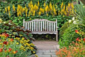 WOLLERTON OLD HALL, SHROPSHIRE: LANHYDROCK BORDERS. HOT, WOODEN, BENCH, PATH, CROCOSMIAS, ACHILLEAS, LIGULARIA THE ROCKET, ACHILLEA, HEMEROCALLIS, ERYSIMUM APRICOT DELIGHT