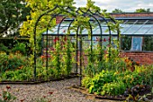 MORTON HALL, WORCESTERSHIRE: THE KITCHEN GARDEN, JULY. ARBOUR, ARCH, ARCHWAY, COVERED IN SWEET PEAS. CLIMBING, CLIMBERS, SUMMER, POTAGER, VEGETABLE, GREENHOUSE