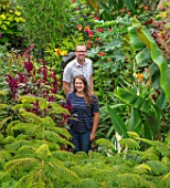 SWEETBRIAR, KENT: STEVE EDNEY, LOUISE DOWLE IN GARDEN WITH BIG LEAVES AND FOLIAGE OF PLANTS. GREEN, PEOPLE, GARDEN, SUMMER, ALBIZIA JULIBRISSIN ROSEA, MUSA SIKKIMENSIS, AMARANTHUS