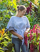 SWEETBRIAR, KENT: LOUISE DOWLE IN THE GARDEN SURROUNDED BY BIG LEAVES AND FOLIAGE OF PLANTS. GREEN, PEOPLE, GARDEN, SUMMER. RICINUS COMMUNIS BLUE GIANT. AMARANTHUS VELVET CURTAINS
