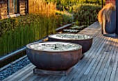 PRIVATE GARDEN, SURREY: DESIGNER ANTHONY PAUL: DECKED GARDEN, CONTAINERS, WATERLILIES. DECKING, ROUND, CIRCULAR, SUNSET, EVENING, LIGHT, FORMAL, SMALL, ENGLISH, COUNTRY