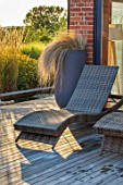 PRIVATE GARDEN, SURREY: DESIGNER ANTHONY PAUL: DECKED GARDEN, CONTAINER WITH STIPA, DECKING, DECKCHAIR, DECK CHAIR, EVENING, LIGHT, FORMAL, SMALL, ENGLISH, COUNTRY