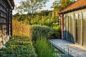 PRIVATE GARDEN, SURREY: DESIGNER ANTHONY PAUL: DECKED GARDEN, DECKING, POND, WATER, EQUISETUM HYEMALE, HORSETAIL, BUILDINGS, CALAMAGROSTIS, FORMAL, SMALL, ENGLISH, COUNTRY